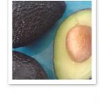 Närbild på två hela avokados och delad, mot en turkos bakgrund.