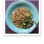 Bönor, ris och grönsaker i en matig gryta på ett turkosfärgat fat.