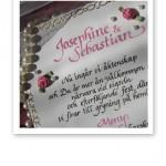 Handtextat inbjudningskort till bröllop i rosa, vitt och guld.