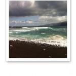 Piskande gråturkosfärgat hav, vitt skum, blå himmel under oroliga mörka moln.