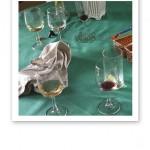 Tomma vinglas och använda servetter på en grön duk, dagen efter en fest.