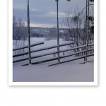 En bit av en snötyngd gärdsgård, med tre uppåtstående käppar och 6 stycken diagonala.