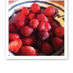 Ett blåvitt keramikfat med röda, rensade jordgubbar.