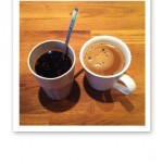 En hög mugg svart kaffe och en mugg med kaffe och mjölk.