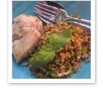 Grillad kyckling och bovete med en grön basilikakvist samt en sked och en gaffel på en turkos tallrik.