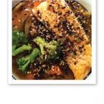 Närbild på en skål lax, rix och grönsaker med sesamfrön strödda ovanpå.