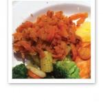 Närbild på ett fat med orange, mjölksyrade morötter och andra grönsaker i periferin.