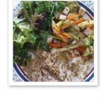 En tallrik med tillagade grönsaker, sallad och råris.