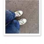 Ett par ben med baggy jeans och Converse-skor, fotade uppifrån.