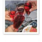 Närbild på fyra glas som skålar i rosa bubbel.