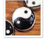 Svartvita yin och yang-symboler mot träunderlag.