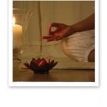Närbild på en yogandes hand på knät, med tumme mot pekfinger, och tända ljuslyktor.