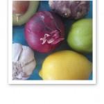 Närbild på en bit rödlök, gul citron, grön lime, vit vitlök, avokado och jordärtskocka.