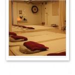 Bild inifrån yogastudion, med vita mattor på golvet och gongongen i bakgrunden.