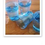 Tre turkosblå vattenglas med vatten i och ett liggande i en pöl av vätska