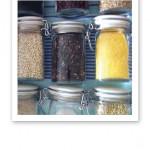 Närbild på glutenfria gryner, korn och ris i glasburkar.