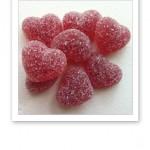 Närbild på åtta stycken rosaröda sockrade geléhjärtan.