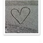 Ett ritat hjärta på marken, i pudersnö.