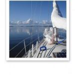Fören på en segelbåt, stilla vattenyta och vita moln på en blå himmel.