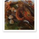 Närbild på skaldjurstallrik med räkor, havskräftor, hummer och diverse musslor.