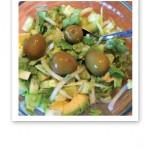 Fyra gröna oliver på toppen av en sallad.