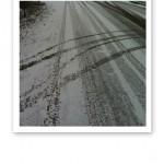 Spår efter bildäck i snön, både parallella och korsande.