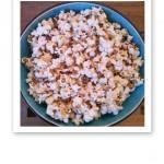 En turkosfärgad skål med vita popcorn.