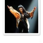 Närbild på Loreen, ensam på scenen med armarna sträckta upp ovanför sig.