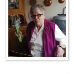 Mormor med en bukett lila tulpaner i handen.
