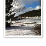 Vintervy över träd, en väg, berg och åkerslänt med klarblåhimmel och vita moln.