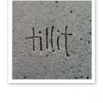 """Ordet """"tillit"""" skrivet med gemener i pudersnö på asfalt."""