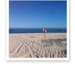 Sandstrand, blå himmel, blått hav och en röd livboj på en pinne.