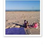 Yogamatta, sandstrand, havet, rosa Converse-skor och vattenflaskor.