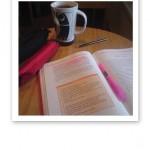 Uppslagen studiebok på ett cafébord, pennfodral och en kopp te.
