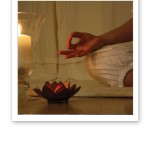En yogis hand i gyan mudra, en yogamatta och tända ljus.