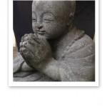 Stenbuddha i pose med händerna ihop framför bröstet.