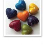 Sju små stenhjärtan i chakrafärgerna.
