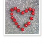 Röda vinbär placerade i hjärtform, mot stenbakgrund.