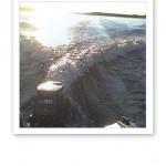 Vy över svallvågor som dras upp bakom en båt, en solig sommardag.