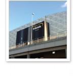 Fasaden på Friends Arena, mot en blå himmel som bakgrund.