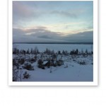 Vintervy över sjön, täckt med is och snö.