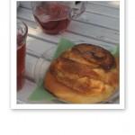 En kanelbulle och två glas saft på ett cafébord i en trädgård.