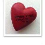 """Rött stenhjärta med texten """"kärleken övervinner allt"""" på latin."""