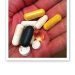 Kosttillskott, kapslar och tabletter i en handflata.