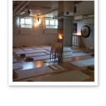 Yogasal på IMY, med vita yogamattor, filtar, kuddar, väggar, fönster och inredning.