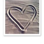 Ett hjärta ritat i beige sandstrandssand.