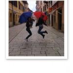 Söta kollegor hoppar på öppen gata med paraplyer i händerna.