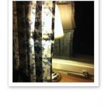 En vit lampa i ett fönster, bakom en blåblommig gardin.