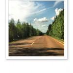 Bilväg i skogen, med blå himmel ovanför och solsken.