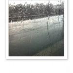 Regnränder på en ruta, med en tågperrong i bakgrunden.